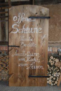 Holztür zur offenen Scheune mit Hinweistext von Familie Beelitz auf die Ausstellung vom Flachs zu Leinen